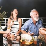 senior couple and friends laughing over dinner