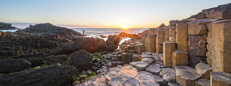 Tourist at Sunset over Giants Causeway Northern Ireland