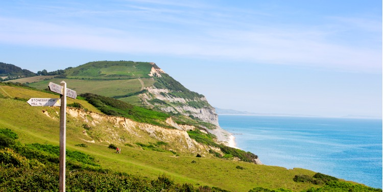 an image of a signpost on a Jurassic Coast walking trail, with the Golden Cap in the background