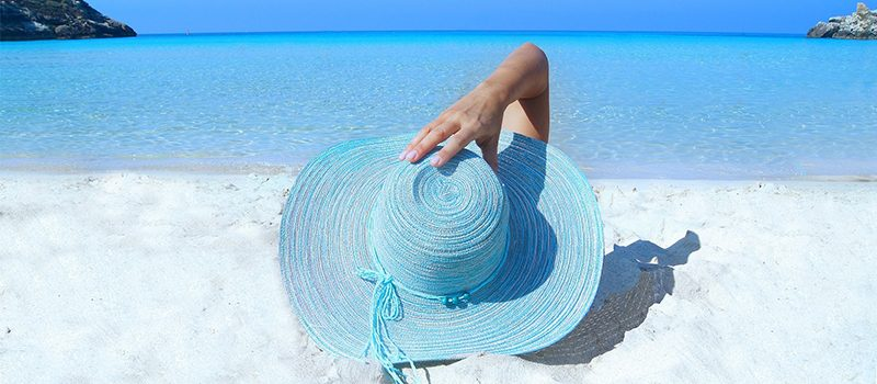 Blue-sun-hat-on-white-sand-beach-clear-blue-sea