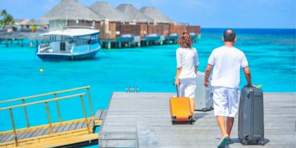 Couple walking with luggage on dock