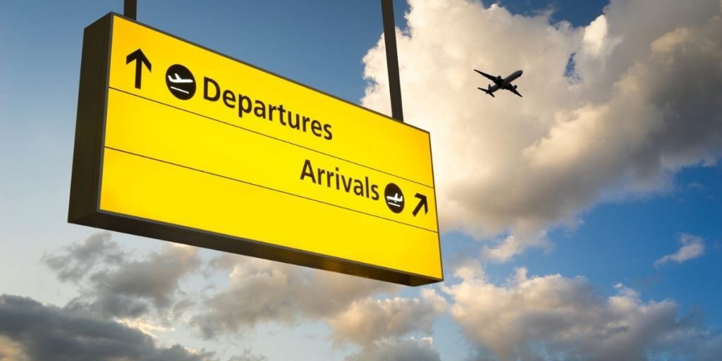 departures sign with sky backdrop