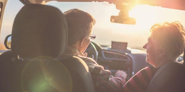 senior couple driving at sunset