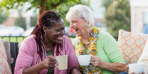 two senior female friends laughing over coffee
