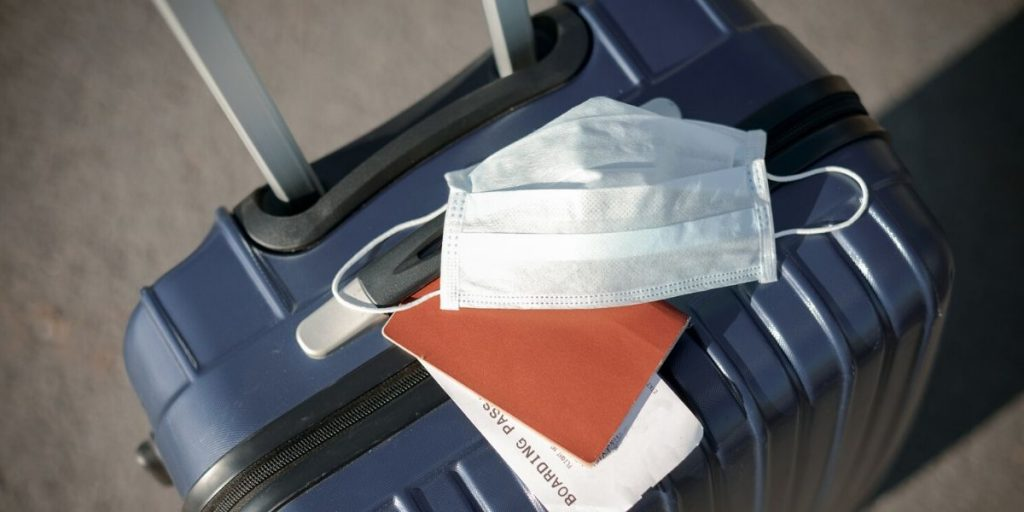 Suitcase with medical mask and boarding pass