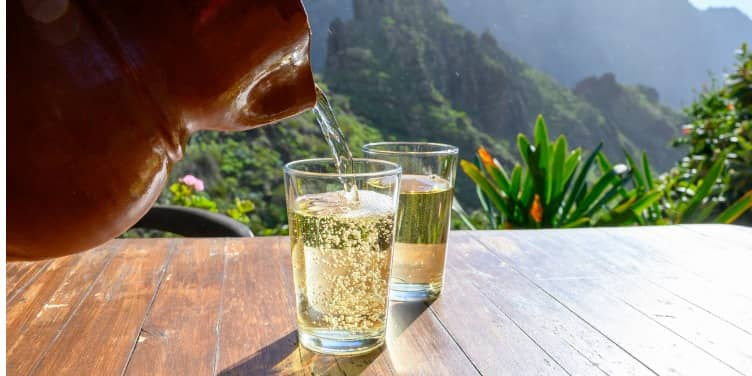 A jug of wine being poured into glasses overlooking green valleys in Tenerife