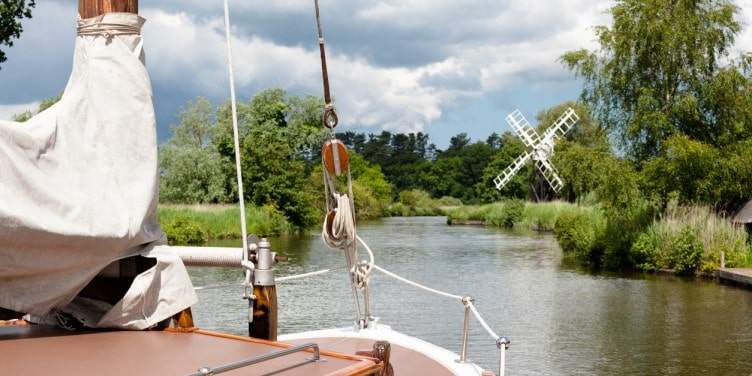 Boat sailing on the Norfolk Broads with a windmill in the background and windmill on river on Norfolk Broads