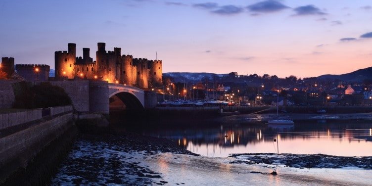 A view of Conway Castle and the harbour at dusk