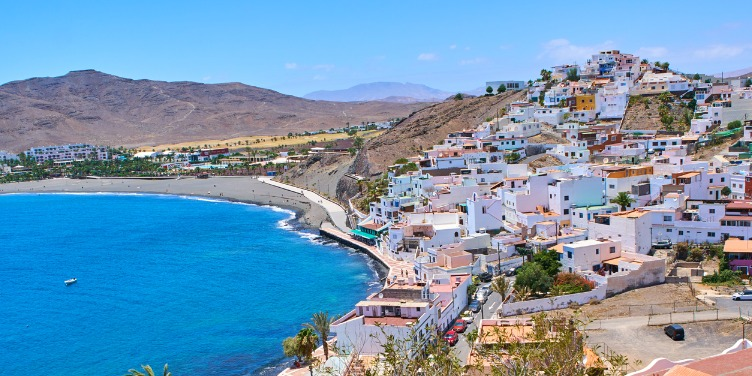 an image of Las Playitas, Fuerteventura with multicolour houses staggered up a hill on the coast