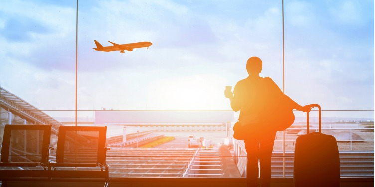 an image of a traveller watching a plane take off in the airport before boarding their flight