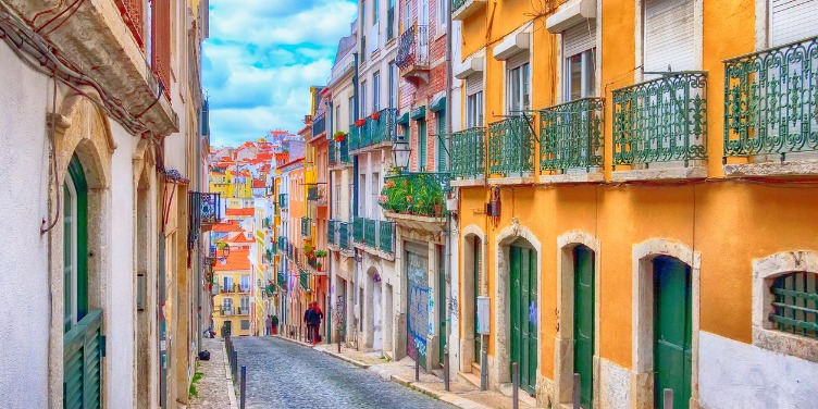 an image of a city street in Lisbon, Portugal with an amber-painted building