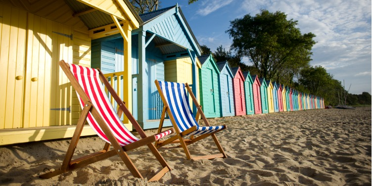 an image of two deck chairs in front of beach huts on a beach in the UK
