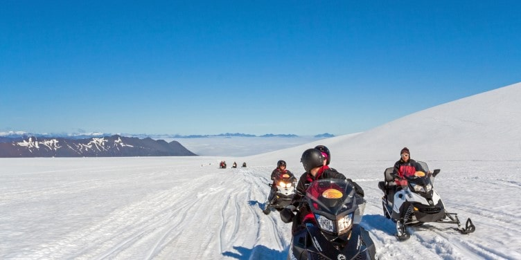 Group of people riding snowmobiles in a glacier in Iceland